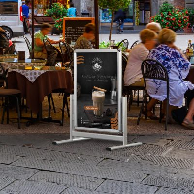 22x28 Al Maki Silver Aluminum Sidewalk Sign outside of an outdoor restaurant seating area