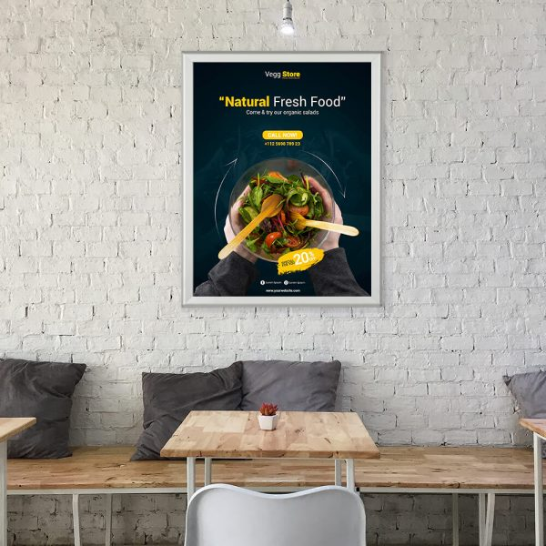 A snap poster hanging on a white brick wall in a small cafe