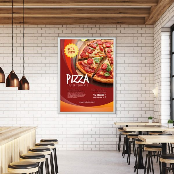 Pizza Poster Template hanging in a snap poster frame on a white subway tile wall in a pizzaria