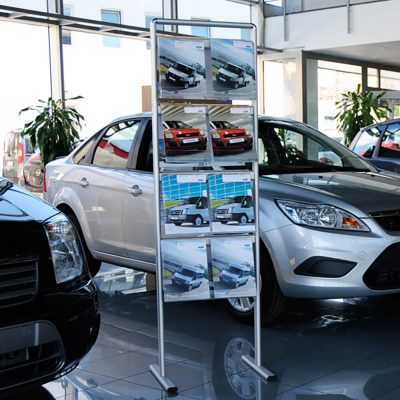 A standing brochure rack with car adverts in a car dealership