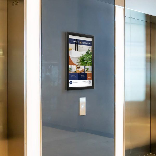 A slide in frame poster in between two elevators in the hallway