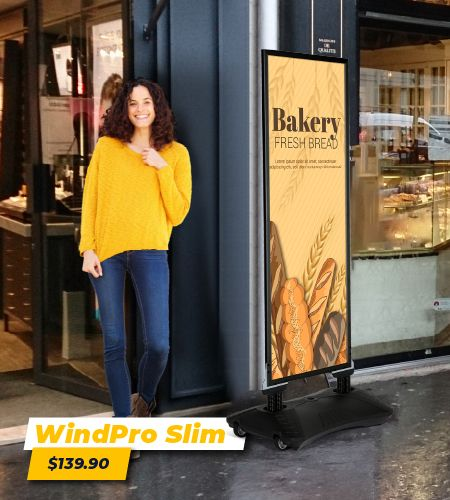 woman with curly hair and a yellow sweater standing outside a bakery in front of a slim mobile banner that is advertising bakery fresh bread